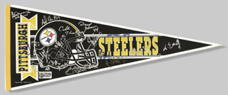 THE PITTSBURGH STEELERS - ANNOTATED PENNANT SIGNED CIRCA 1991 CO-SIGNED BY: JOE MEAN JOE GREENE, THOMAS EVERETT, JEFF BRADY, AARON JONES, BUBBY BRISTER, JERRY OLSAVSKY, DAVID JOHNSON, ADRIAN COOPER, CARLTON HASELRIG, RICHARD SHELTON, BARRY FOSTER, RICK STROM, DAVID LITTLE, JUSTIN STRZELCZYK, CHUCK NOLL