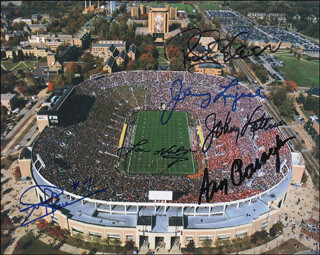 THE NOTRE DAME FOOTBALL TEAM - AUTOGRAPHED SIGNED PHOTOGRAPH CO-SIGNED BY: ROBERT P. ROCKY BLEIER, JOHNNY LUJACK, JOHNNY LATTNER, JOE THEISMANN, LOU HOLTZ, ARA R. PARSEGHIAN
