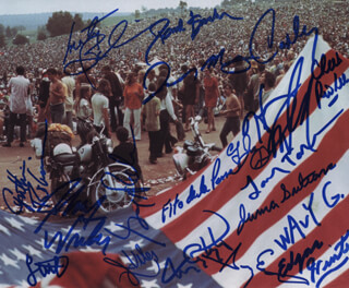 WOODSTOCK - AUTOGRAPHED SIGNED PHOTOGRAPH CO-SIGNED BY: TEN YEARS AFTER (RIC LEE), JEFFERSON AIRPLANE (MARTY BALIN), JOSEPH COUNTRY JOE McDONALD, JEFFERSON AIRPLANE (PAUL KANTNER), GREGG ROLIE, TOM CONSTANTEN, JOHNNY WINTER, EDGAR WINTER, WAVY GRAVY, SLY AND THE FAMILY STONE (CYNTHIA ROBINSON), SLY AND THE FAMILY STONE (JERRY MARTINI), JUMA SULTAN, JERRY VELEZ, CANNED HEAT (HARVEY MANDEL), STEVE KAYE, CANNED HEAT (LARRY THE MOLE TAYLOR), CANNED HEAT (ADOLFO FITO DE LA PARRA), MOUNTAIN (CORKY LAING), SLY AND THE FAMILY STONE (GREG ERRICO)